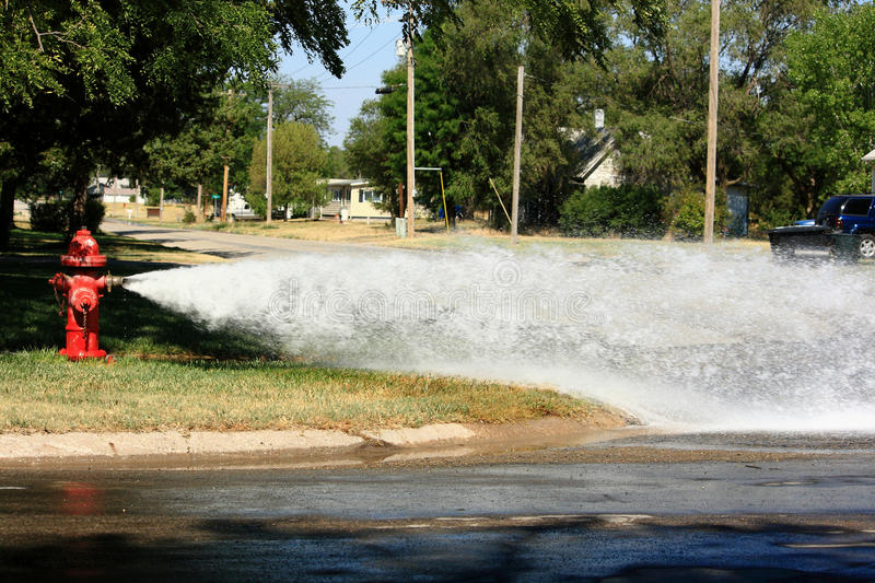 Open Fire Hydrant Gushing Water Into The Street. An open fire hydrant gushing a high pressure stream of water into the intersection of a quiet residential stock photos