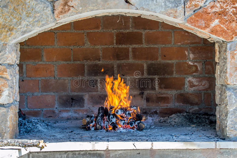 Open fire place oven. An outdoor open fireplace oven for barbecue or baking, in brick and stone with fire burning stock images