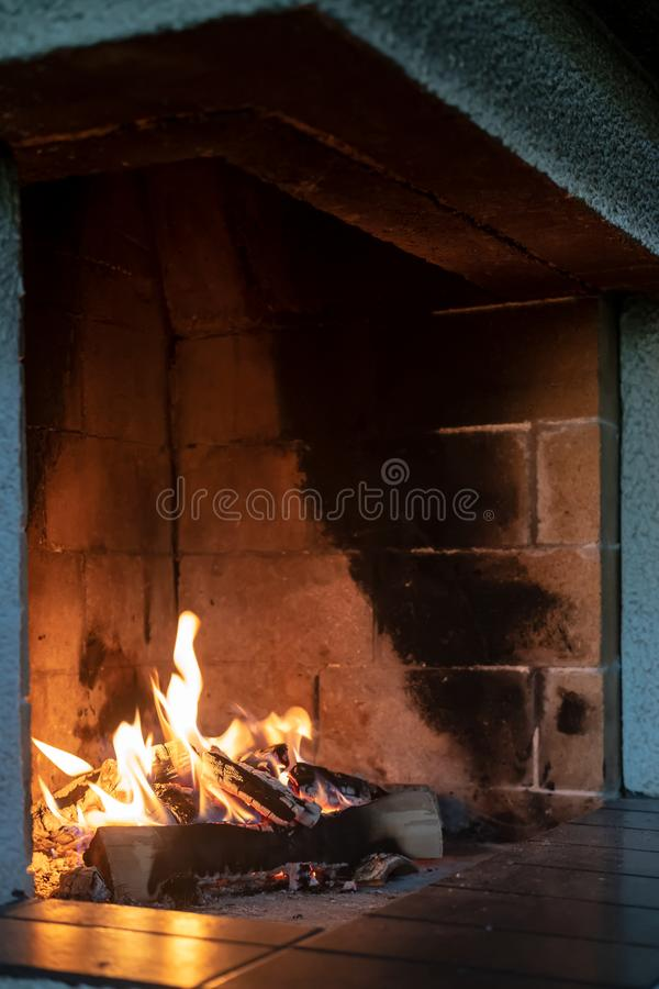 Open fireplace, firewood and fire, giving heat, on a cold winter evening, in a cozy house. stock image
