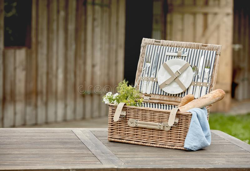 Open fitted wicker picnic hamper on a garden table. Open fitted wicker picnic hamper with plates, cutlery and French baguettes on a garden table outside a timber stock photography
