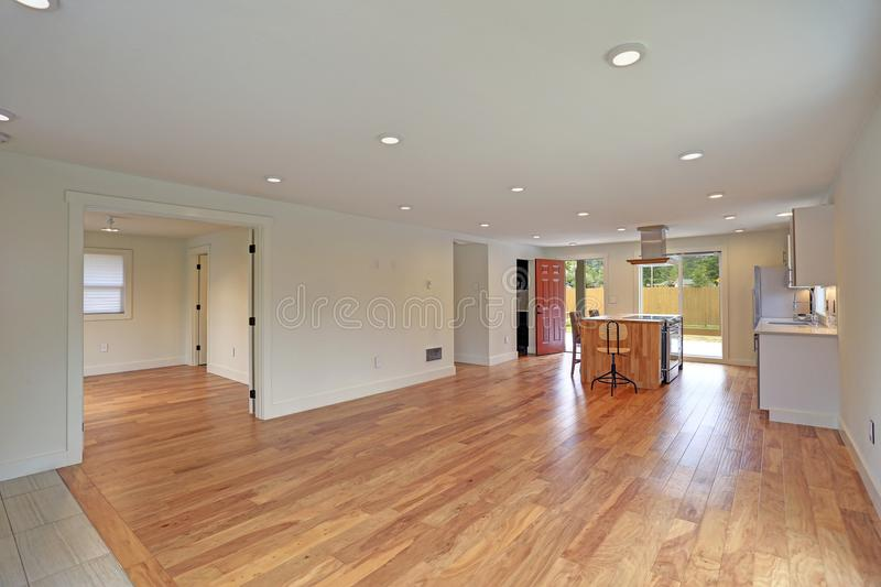 Open floor plan interior features a newly remodeled kitchen. With empty dining space accented with glossy hardwood floors and white ceiling dotted with pot stock photography