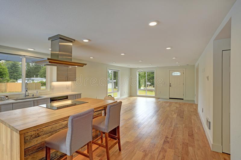 Open floor plan interior features a newly remodeled kitchen. With empty dining space accented with glossy hardwood floors and white ceiling dotted with pot stock photo