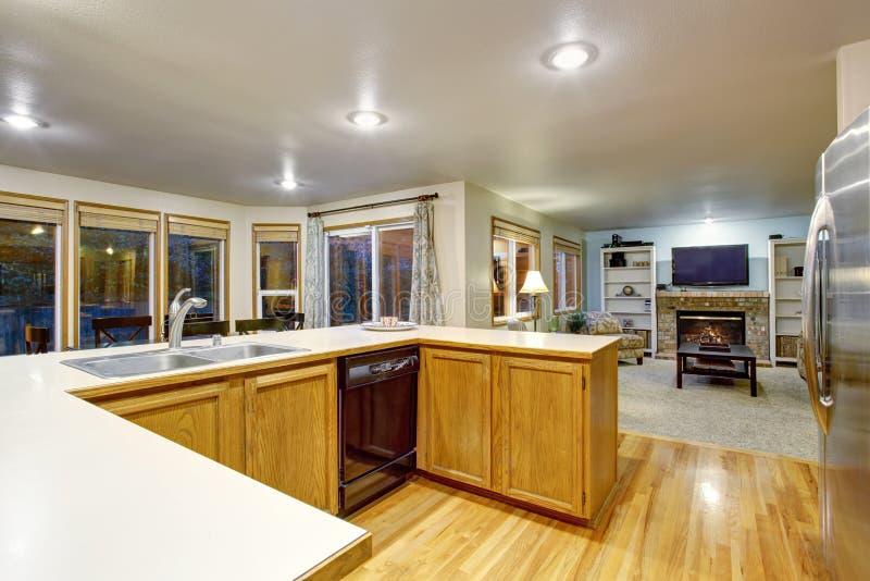 Open floor plan kitchen interior with brown cabinets and hardwood floor stock photos