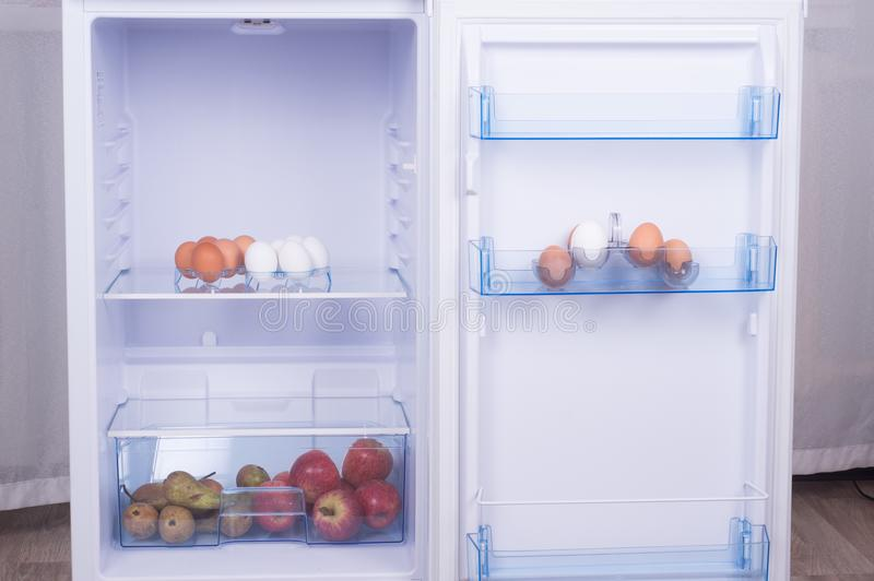 Open fridge, eggs, pears and apples on the shelf of refrigerator stock images