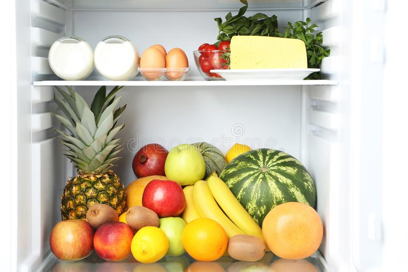 Open fridge. Full of fruits with cheese and bottle of milk stock photo