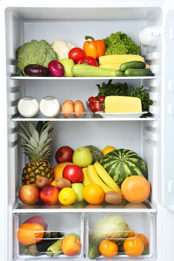 Open fridge. Full of vegetables and fruits stock image