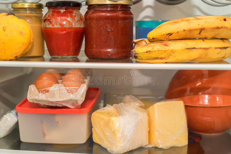 Open fridge with usual food. Open fridge with usual daily food of average man stock photo