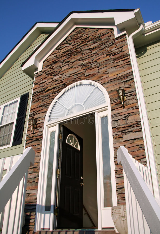Open front door of a home with a stone facade. royalty free stock photo