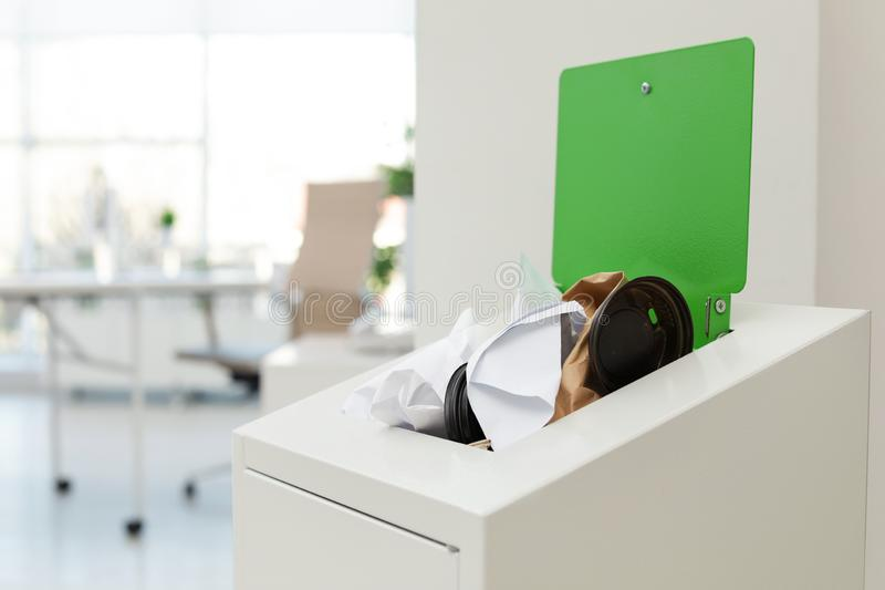 Open full trash bin in modern office. Waste recycling. Open full trash bin in modern office, space for text. Waste recycling royalty free stock photography