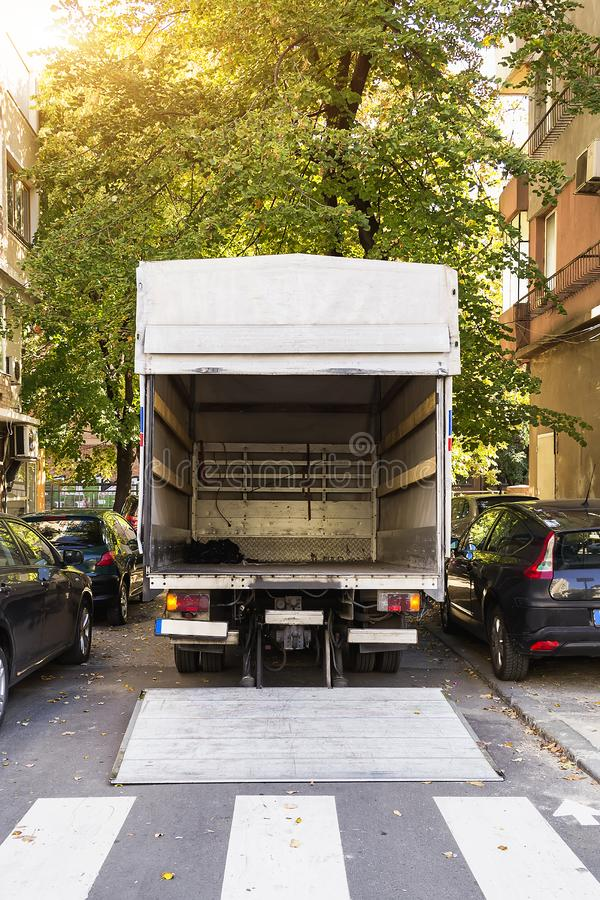 Open furniture delivery truck on a city street. Empty moving van with rear doors opened. On an autumn sunny day royalty free stock photography