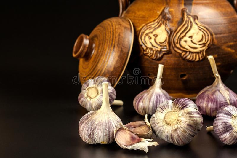 Open garlic on black background table. Whole and split fresh garlic on a black background. Traditional flu and cold treatment. Aro stock photos