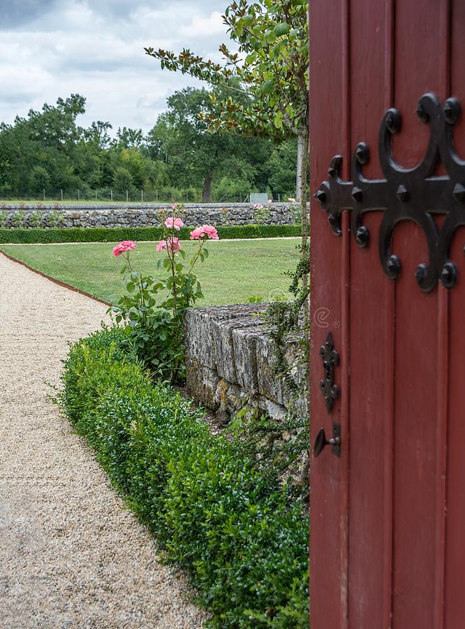 An open gate invites you to the garden with roses stock image