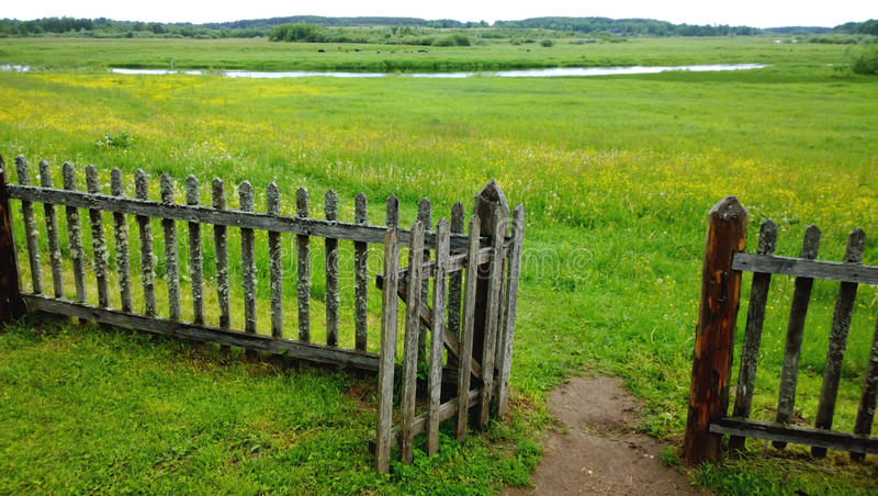 An open gate in a wooden fence and a green meadow beyond it, the path in the frame . Cloudy summer or late spring stock image