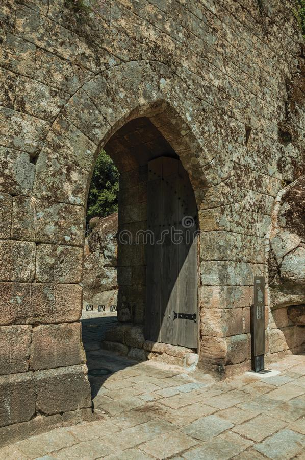 Open gateway with wooden door on a stone wall. Open entrance gate with wooden door on a stone wall in a sunny day, at the historic city center of Sortelha. One royalty free stock photography