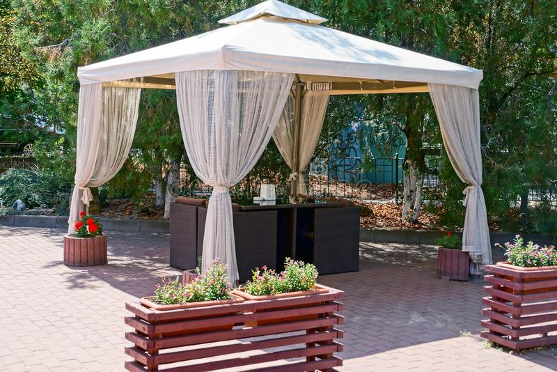 Outdoor gazebo with curtains and furniture on the sidewalk in the park stock photography
