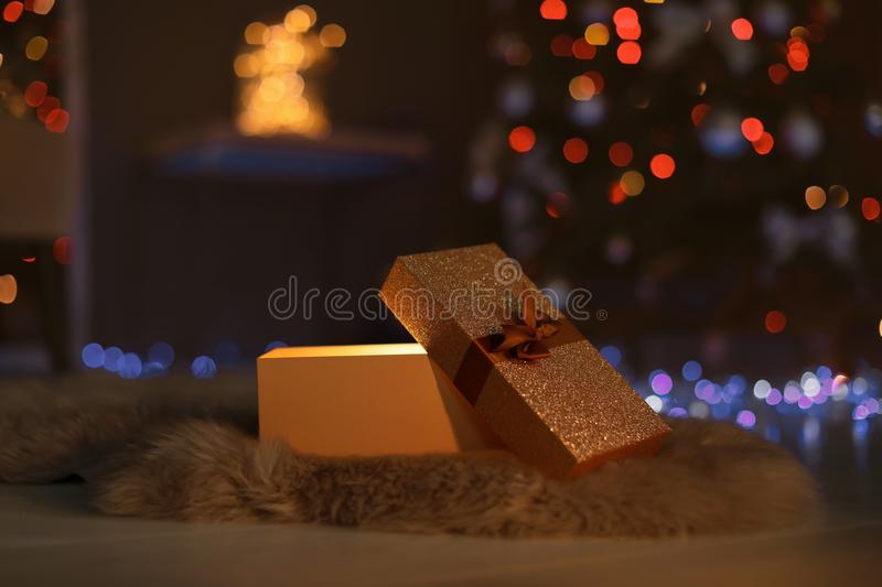 Open gift box and Christmas tree in room royalty free stock photography