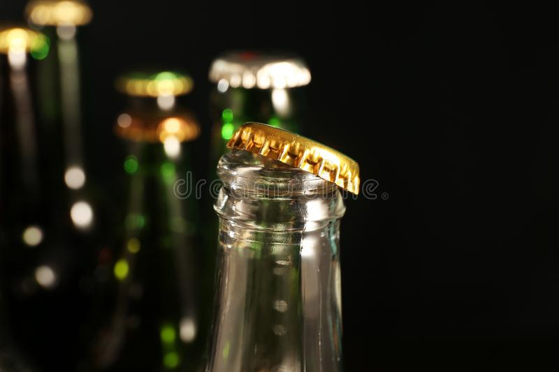 Open glass bottle of cold beer on dark background, closeup royalty free stock images