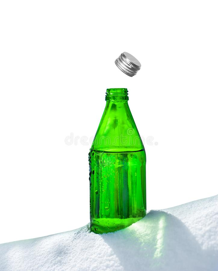 Open glass bottle of mineral water in snow royalty free stock photography