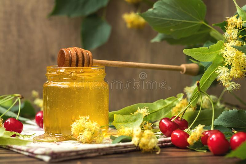 Open glass jar of liquid honey and honey dipper, bunch of linden royalty free stock images