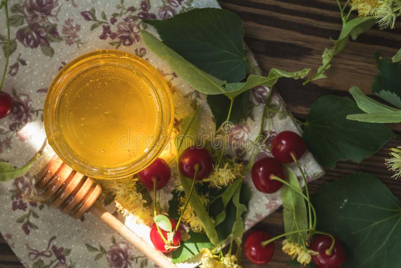 Open glass jar of liquid honey and honey dipper, bunch of linden stock photography