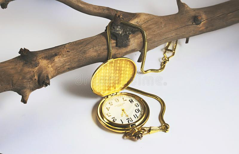 Open gold pocket watch against a white background with a fob chain royalty free stock photos