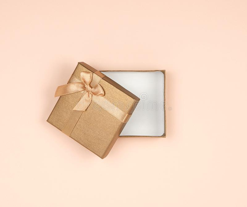 open golden gift box with a bow on a beige background stock image