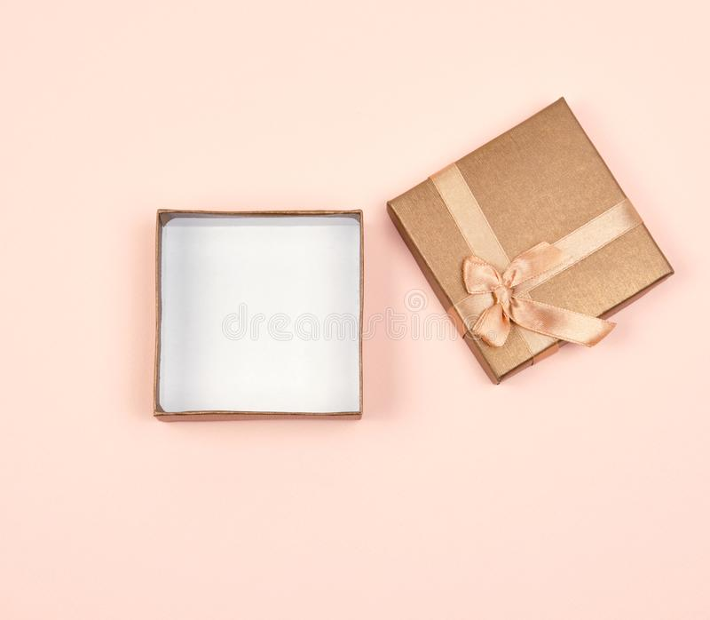 open golden square gift box with a bow on a beige background royalty free stock photos