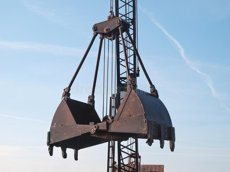 Open grab bucket. And crane on working site royalty free stock image