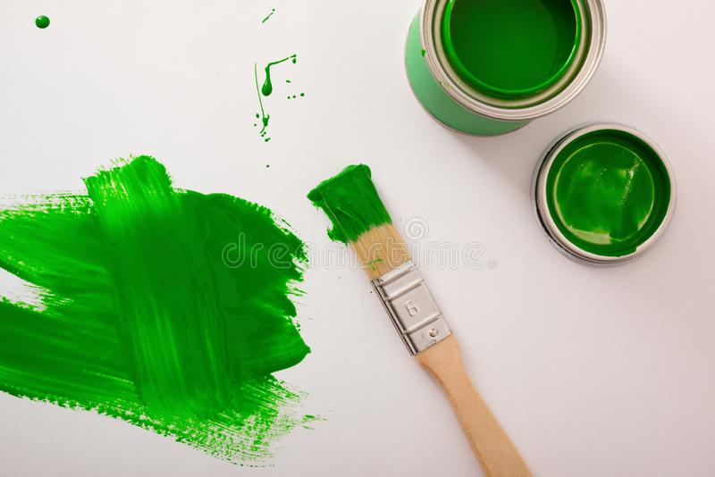Open green paint canister on white table painted with brush royalty free stock photo