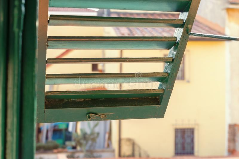 Open green trellis window overlooking the italian city in tuscany. Open old green shutters on a city street in Italy on a sunny day royalty free stock images