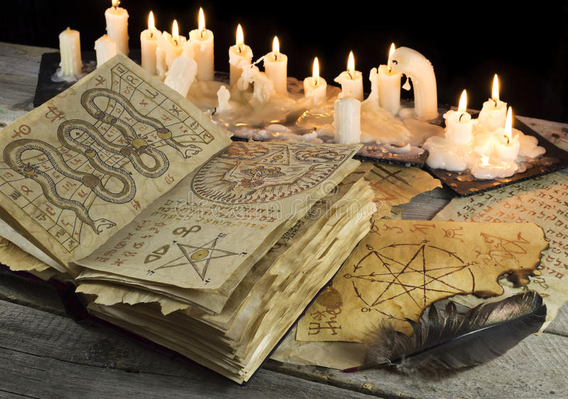 Open Grimoire book with candles and quill royalty free stock photos
