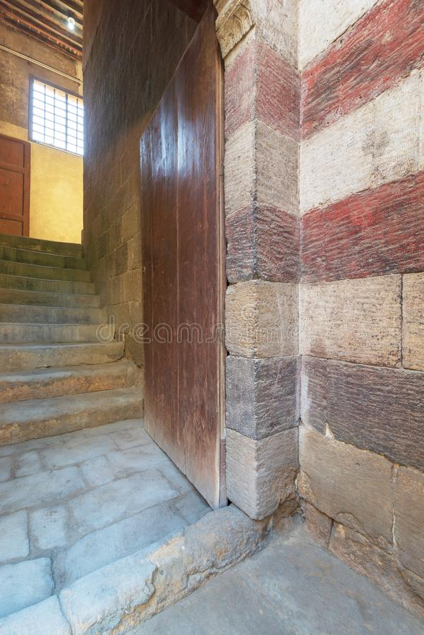 Open grunge wooden door revealing old stone staircase going up, Cairo, Egypt. Open grunge wooden door revealing old stone staircase going up leading to Bayt al stock photos