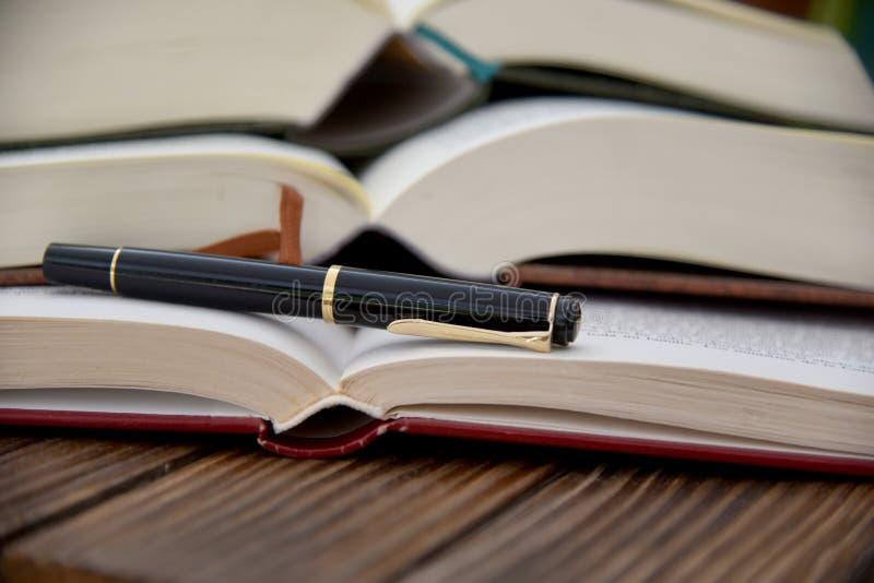 Open ha impilato i libri e lo stile della piuma immagini stock libere da diritti