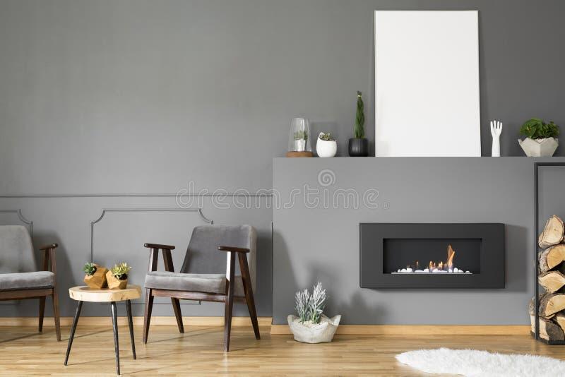 Open haard in het kader van lege affiche met model in grijze woonkamer int. royalty-vrije stock fotografie