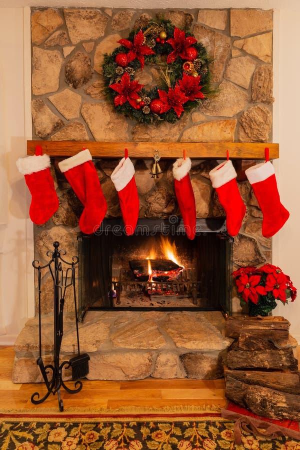 Open haard met zes Kerstmiskousen, logboeken, klokken en kroon stock afbeelding