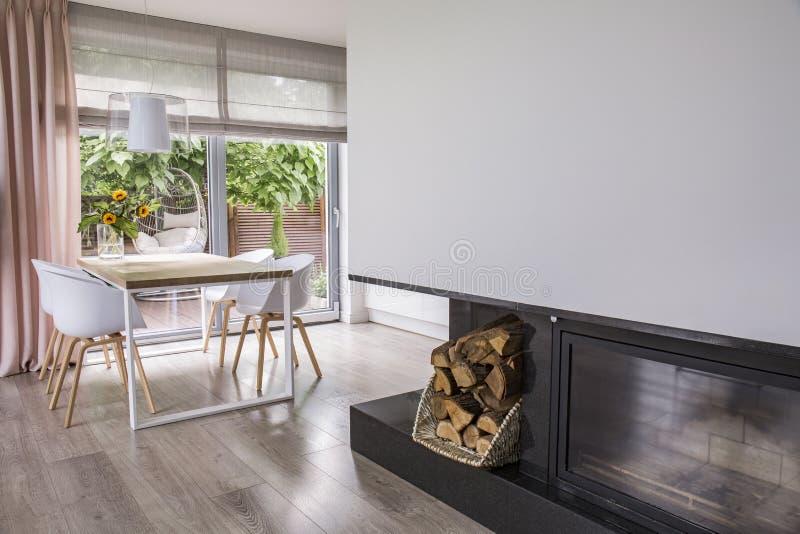 Open haard naast witte stoelen bij lijst in helder eetkamerbinnenland met venster Echte foto stock foto's