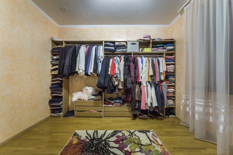 Open habillant la garde-robe de cabinet compl?tement du m?le diff?rent et les v?tements et les accessoires color?s femelles sur l image stock