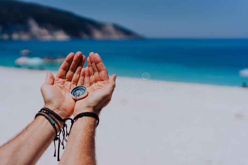Open hand palms holding metal compass against sandy beach and blue sea. Searching your way concept. Point of view pov stock photography