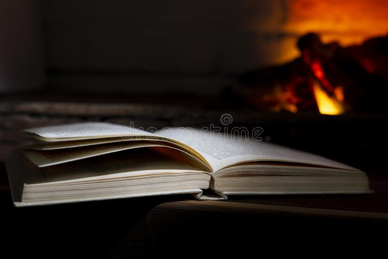 An open hardback book lies near a burning fireplace.  royalty free stock image