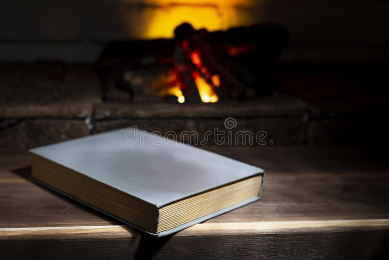 An open hardback book lies near a burning fireplace.  royalty free stock images