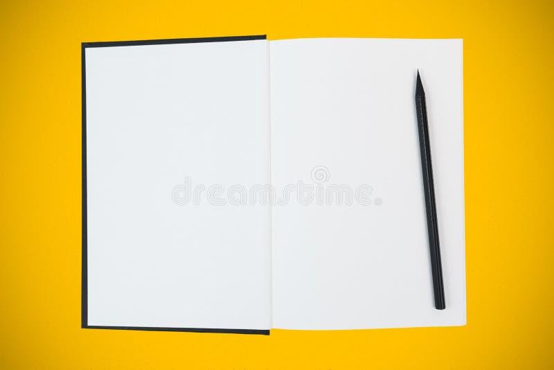 Open hardcoverboek met lege witte pagina's en zwart houten potlood op gele achtergrond stock foto