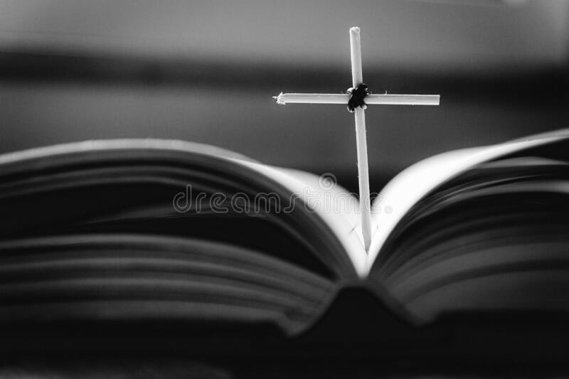 Open Holy Bible book and homemade cross. Close-up view royalty free stock photography