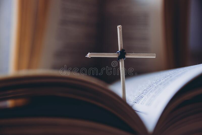Open Holy Bible book and homemade cross. Close-up view royalty free stock image