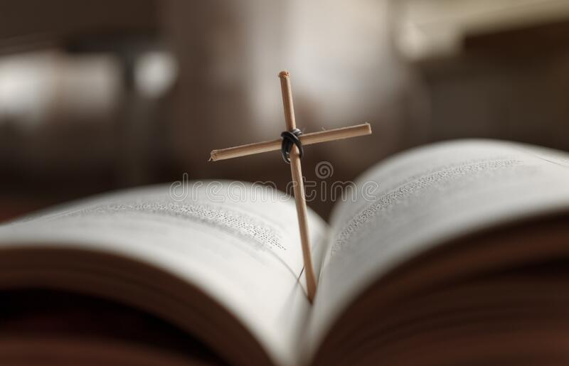 Open Holy Bible book and homemade cross. Close-up view royalty free stock photo