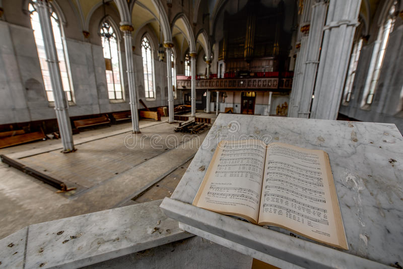 Open Holy Bible in Pulpit - Abandoned Church. A wide interior view of an open holy bible at the pulpit looking out towards an empty, abandoned church royalty free stock photos
