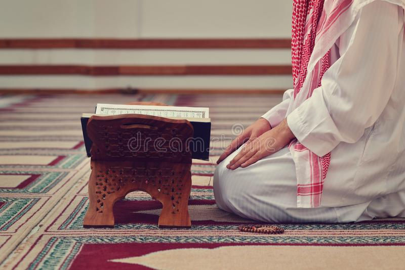 An open Holy quran with wood stand with praying people in background royalty free stock photo