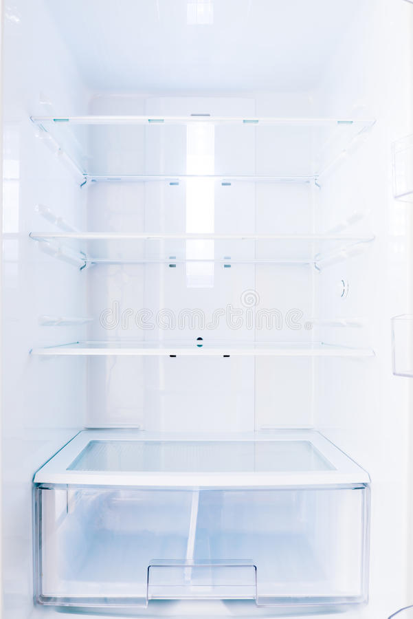 An open home based fridge with empty shelves royalty free stock image