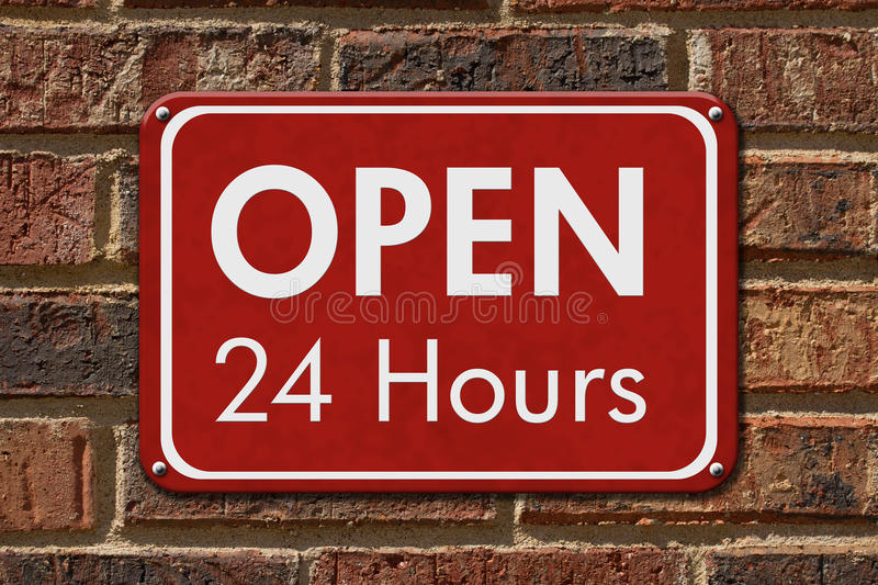 Open 24 Hours Sign. A red hanging sign with text Open 24 Hours on a brick wall royalty free stock photos