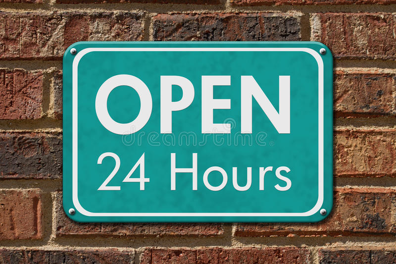 Open 24 Hours Sign. A teal sign with text Open 24 Hours on a brick wall stock photo