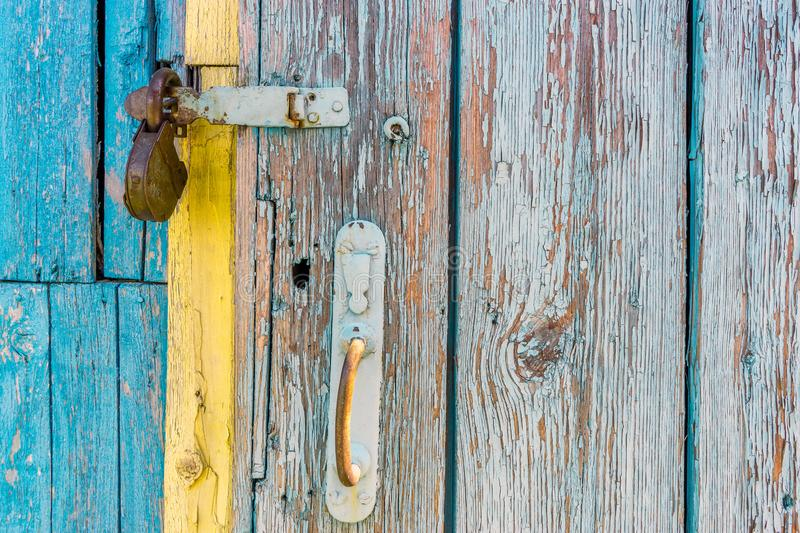 Open iron padlock on a battered wooden door with weathered cracks of blue and yellow colors of old country house stock photography